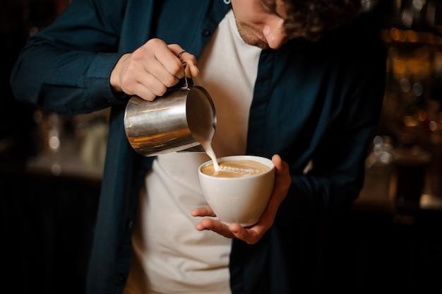 Młody barista wlewając mleko do filiżanki kawy
