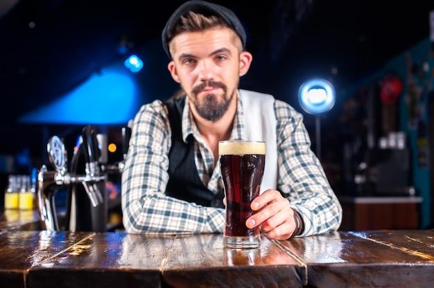Młody barman nalewa do szklanek świeży napój alkoholowy, stojąc przy barze w barze