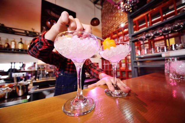 Młody barman przygotowuje koktajl w barze. pokaz barmana