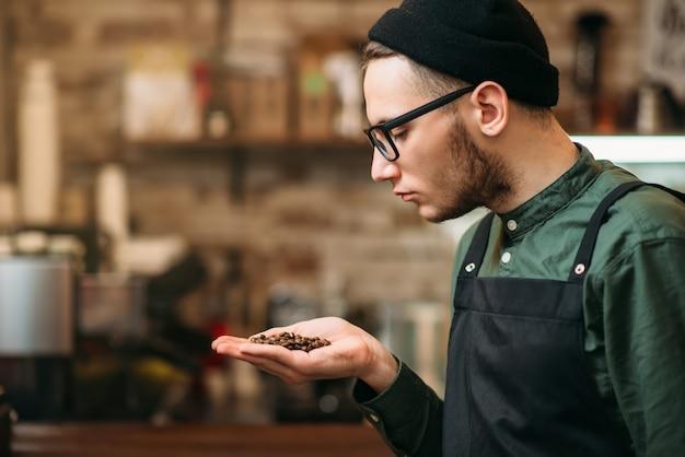 Młody barman trzyma w dłoni ziarno kawy i cieszy się aromatem.
