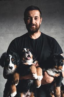 Młody, berneński pies pasterski w rękach. zbliżenie, zdjęcie studio. pojęcie opieki, edukacji, szkolenia i hodowli zwierząt
