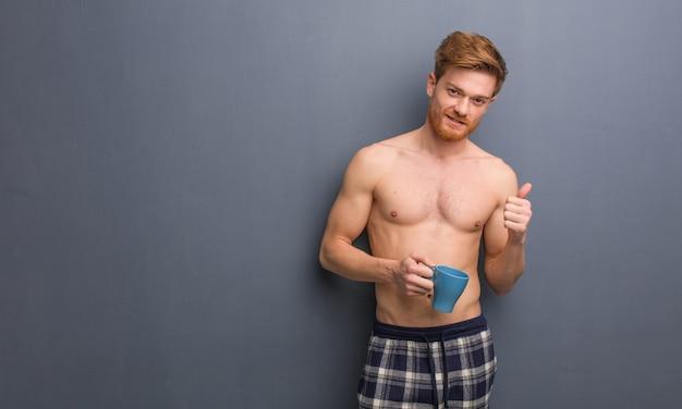Młody bez koszuli rudzielec mężczyzna ono uśmiecha się i podnosi kciuk up. trzyma kubek kawy.