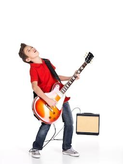 Młody biały chłopiec śpiewa i gra na gitarze elektrycznej z jasnymi emocjami, isolatade na białym tle