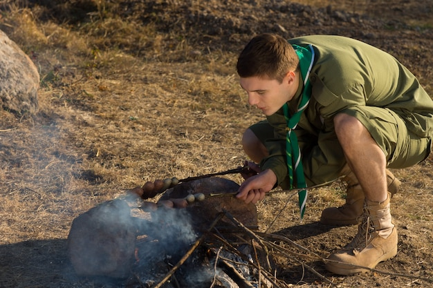 Młody biały harcerz dokonywanie ognia z drewna do gotowania na kempingu.