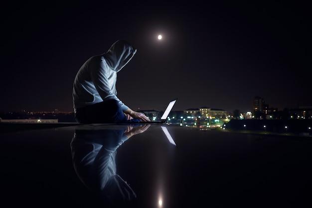 Młody biały mężczyzna siedzi na zewnątrz i pracuje z laptopem w nocy,