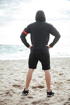 Młody biegacz o pełnej długości na plaży z tyłu