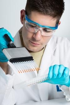 Młody biolog z pipetą wielokanałową
