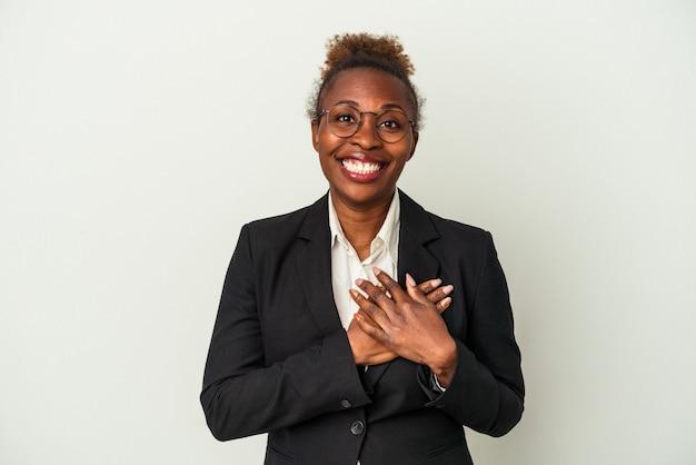 Młody biznes african american kobieta na białym tle ma przyjazny wyraz, naciskając dłoń na klatkę piersiową. koncepcja miłości.
