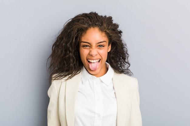 Młody biznes african american kobieta zabawny i przyjazny wystający język.