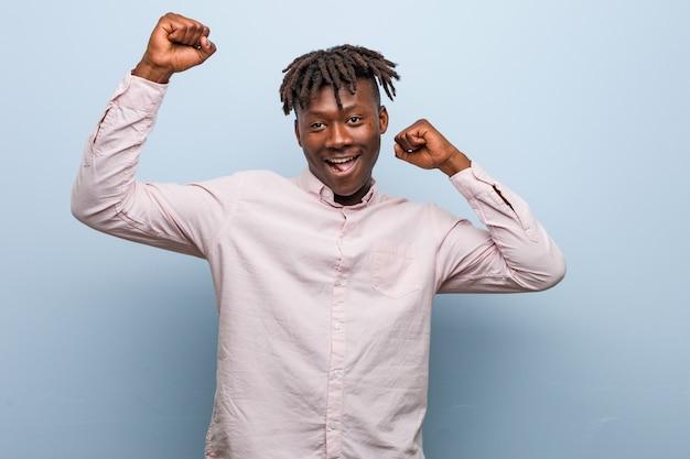 Młody biznes afrykański murzyn świętuje wyjątkowy dzień, skacze i energicznie podnosi ręce.