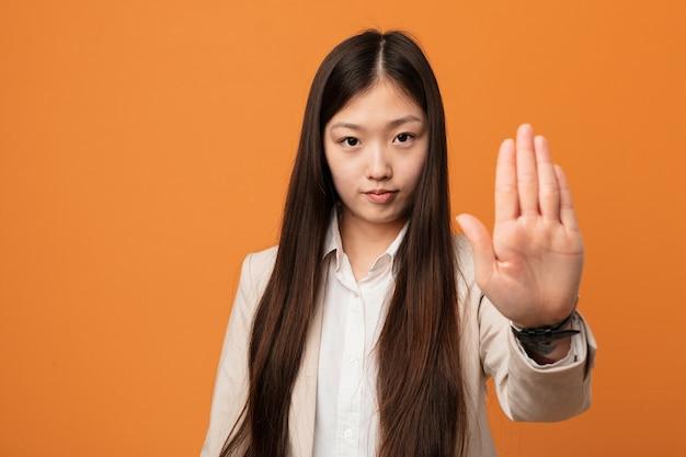 Młody biznes chinka stojąca z wyciągniętą ręką pokazuje znak stopu, uniemożliwiając ci.