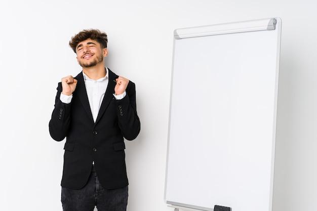Młody biznes coaching arabski mężczyzna podnosząc pięść, czując się szczęśliwy i sukces.
