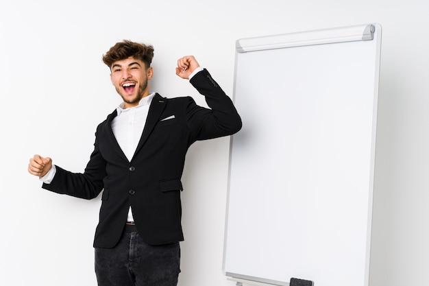 Młody biznes coaching arabski mężczyzna świętuje wyjątkowy dzień, skacze i energicznie podnosi ręce.