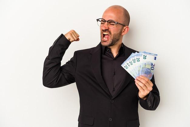 Młody biznes człowiek łysy gospodarstwa rachunki na białym tle podnosząc pięść po zwycięstwie, koncepcja zwycięzca.