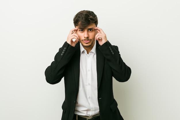 Młody biznes hiszpanin mężczyzna koncentruje się na zadaniu, trzymając palce wskazujące głową.