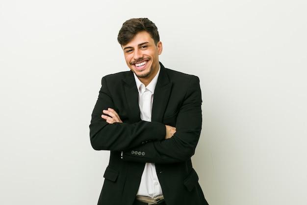 Młody biznes hiszpanin mężczyzna, który czuje się pewnie, krzyżując ręce z determinacją.
