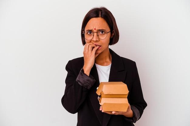Młody biznes indyjska kobieta jedzenie hamburgerów na białym tle gryząc paznokcie, nerwowa i bardzo niespokojna.