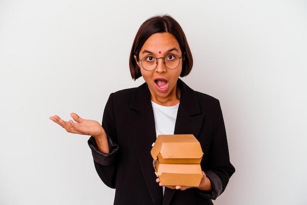 Młody biznes indyjska kobieta jedzenie hamburgerów na białym tle zaskoczony i zszokowany.