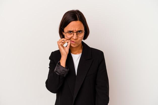 Młody biznes indyjska kobieta na białym tle na białej ścianie z palcami na ustach, zachowując tajemnicę.
