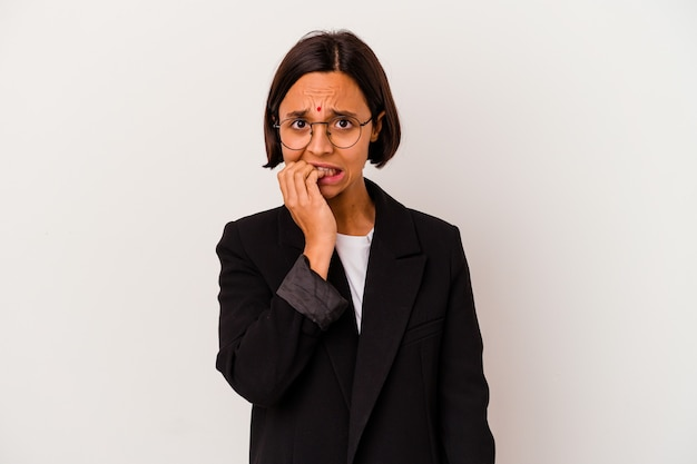 Młody biznes indyjska kobieta na białym tle obgryzając paznokcie, nerwowy i bardzo niespokojny.