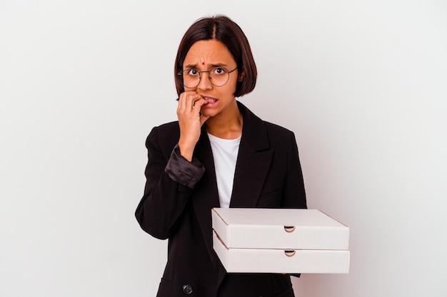 Młody biznes indyjska kobieta trzyma pizze na białym tle, gryząc paznokcie, nerwowy i bardzo niespokojny.