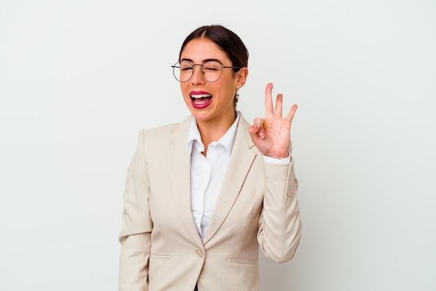 Młody biznes kaukaski kobieta na białym tle mruga okiem i trzyma w porządku gest ręką.