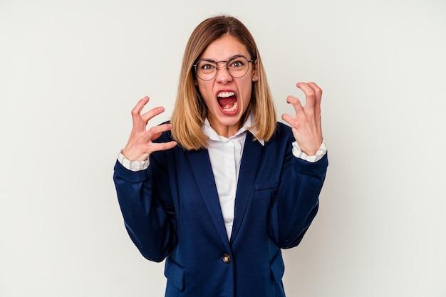 Młody biznes kaukaski kobieta na białym tle na białej ścianie krzyczy z wściekłości