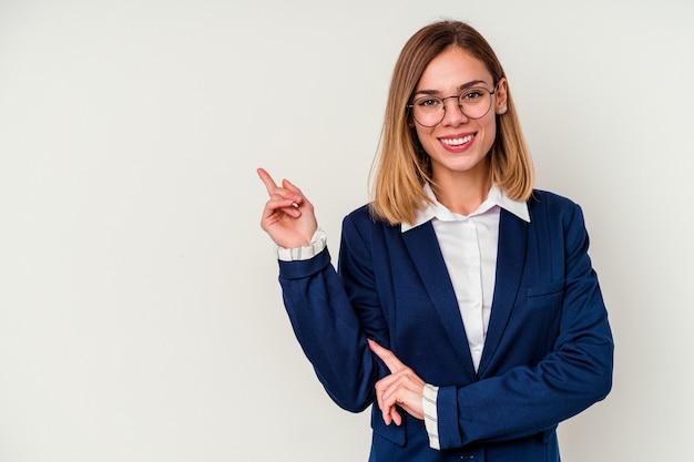 Młody biznes kaukaski kobieta na białym tle uśmiechnięty radośnie wskazując palcem wskazującym od hotelu.
