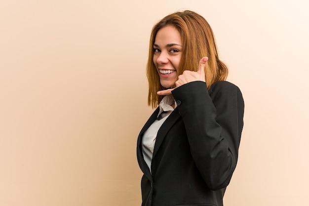 Młody biznes kaukaski kobieta pokazano gest rozmowy telefonicznej z palcami.