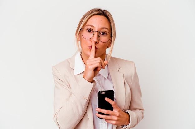 Młody biznes kaukaski kobieta trzyma telefon komórkowy na białym tle na białej ścianie, zachowując tajemnicę lub prosząc o ciszę.