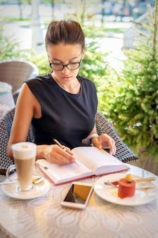 Młody biznes kaukaski kobieta w czarnej sukni pisze w notesie siedząc przy stole w kawiarni