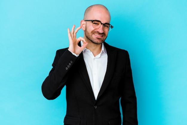 Młody biznes kaukaski łysy mężczyzna na białym tle na niebieskiej ścianie, wesoły i pewny siebie, pokazując ok gest