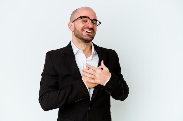 Młody biznes kaukaski łysy mężczyzna na białym tle na niebieskim tle ma przyjazny wyraz, przyciskając dłoń do klatki piersiowej. koncepcja miłości.