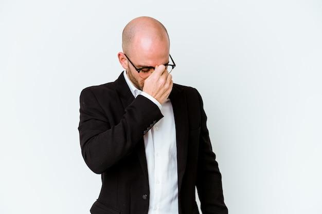 Młody biznes kaukaski łysy mężczyzna na niebiesko o ból głowy, dotykając przedniej części twarzy.