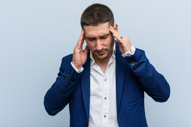 Młody biznes kaukaski mężczyzna dotyka świątyń i ma ból głowy.