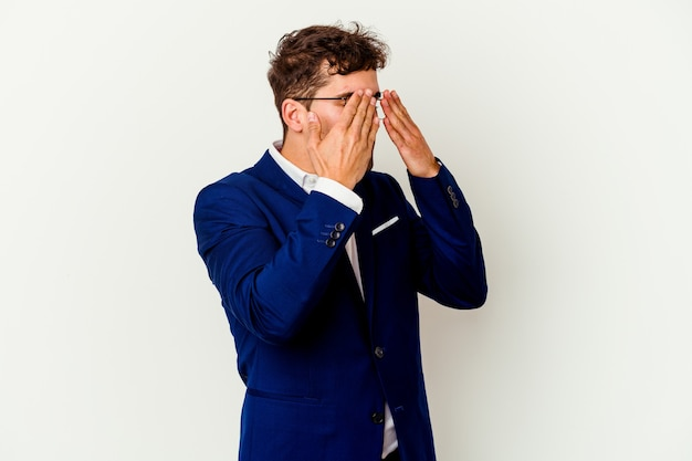 Młody biznes kaukaski mężczyzna na białym tle na białej ścianie boi się zakrywających oczy rękami.