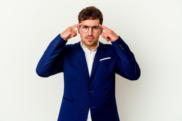 Młody biznes kaukaski mężczyzna na białym tle na białej ścianie koncentruje się na zadaniu, trzymając wskazujące palce wskazujące głowę.