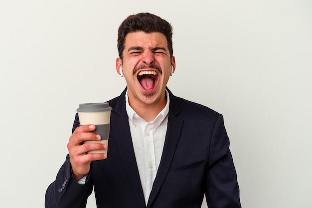 Młody biznes kaukaski mężczyzna nosi bezprzewodowe słuchawki i trzyma kawę drogę na białym tle krzycząc bardzo zły i agresywny.