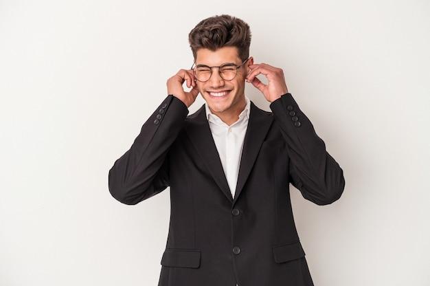 Młody biznes kaukaski mężczyzna nosi słuchawki na białym tle obejmujące uszy rękami.