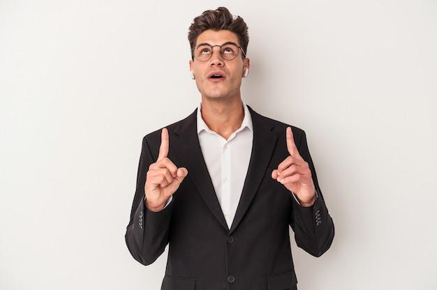Młody biznes kaukaski mężczyzna nosi słuchawki odizolowywające na białym tle wskazuje do góry z otwartymi ustami.