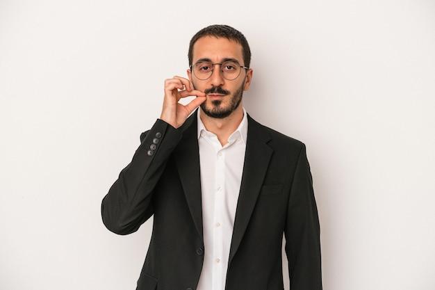 Młody biznes kaukaski mężczyzna odizolowywający na białym tle z palcami na ustach zachowując tajemnicę.