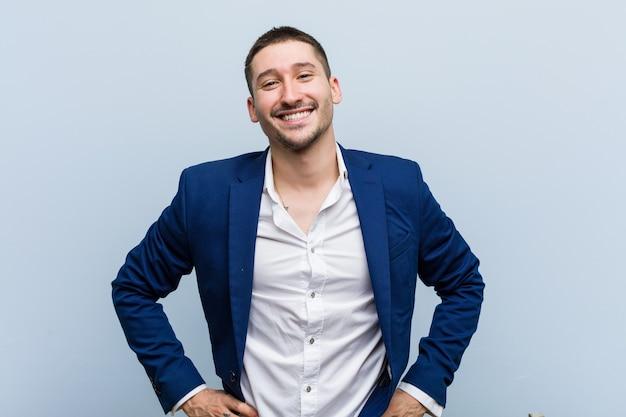 Młody biznes kaukaski mężczyzna pewny siebie, trzymając ręce na biodrach.
