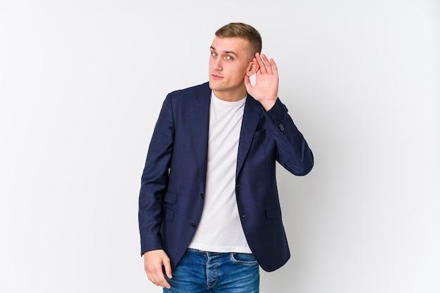 Młody biznes kaukaski mężczyzna próbuje słuchać plotek.