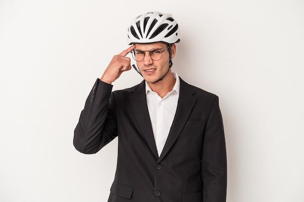 Młody biznes kaukaski mężczyzna trzyma kask rowerowy na białym tle wskazując świątynię palcem, myśląc, koncentrując się na zadaniu.