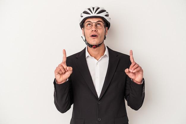 Młody biznes kaukaski mężczyzna trzyma kask rowerowy odizolowywający na białym tle wskazuje do góry z otwartymi ustami.