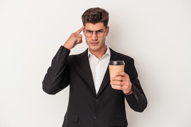 Młody biznes kaukaski mężczyzna trzyma zabrać kawę na białym tle wskazując świątynię palcem, myśląc, koncentrując się na zadaniu.