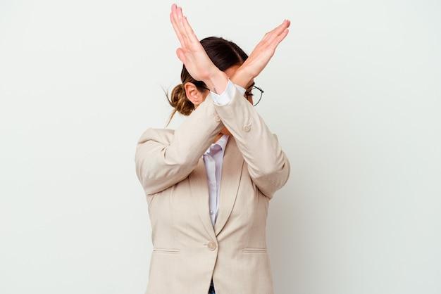 Młody biznes kobieta kaukaski na białym tle trzymając dwie skrzyżowane ręce, pojęcie odmowy.