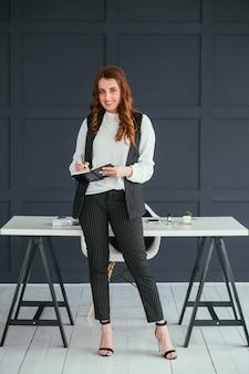 Młody biznes kobieta portret. uśmiechnięty profesjonalista w miejscu pracy