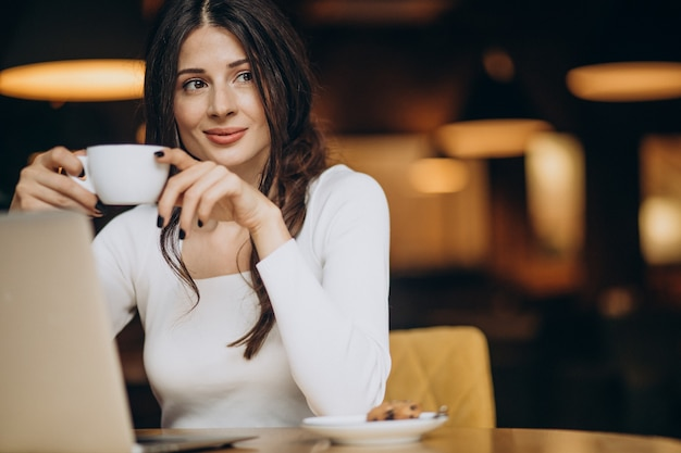 Młody biznes kobieta pracuje na komputerze w kawiarni