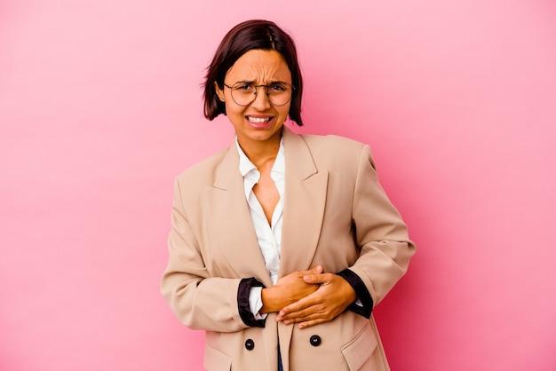 Młody biznes kobieta rasy mieszanej na białym tle na różowej ścianie o ból wątroby, ból brzucha.
